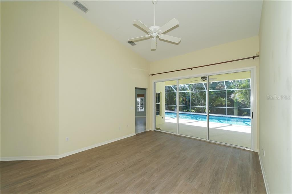Living room with sliders to lanai and pool. - Single Family Home for sale at 1714 79th Ct W, Bradenton, FL 34209 - MLS Number is A4416601