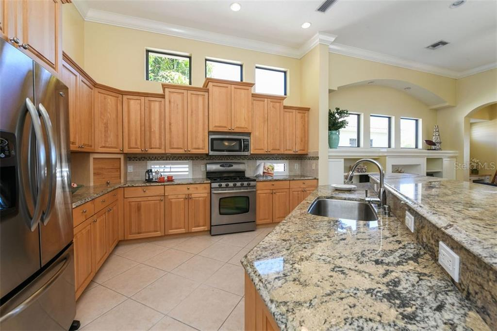 Kitchen with Wood Cabinets, Sparkling Granite & Stainless Steel Appliances - Single Family Home for sale at 7060 Whitemarsh Cir, Lakewood Ranch, FL 34202 - MLS Number is A4417363