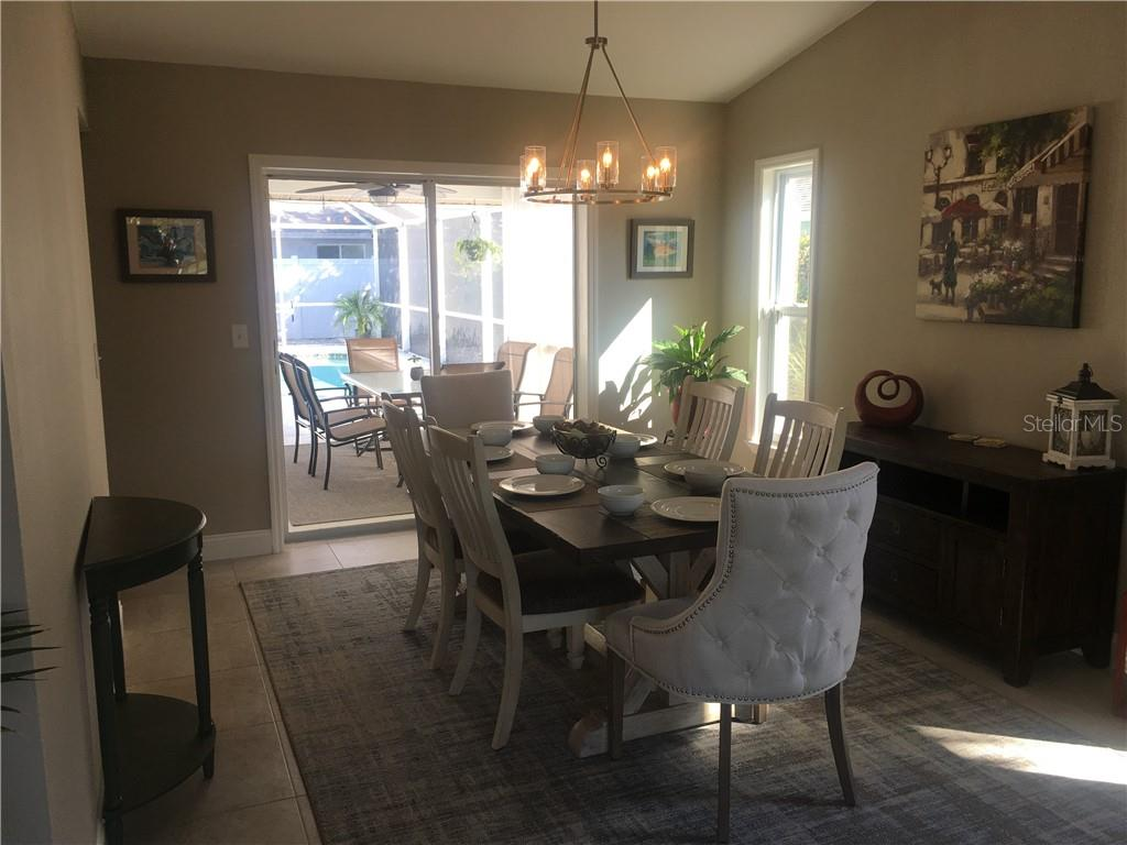 Airy dining room has sliders to patio and sunny pool area. - Single Family Home for sale at 1611 82nd St Nw, Bradenton, FL 34209 - MLS Number is A4417607