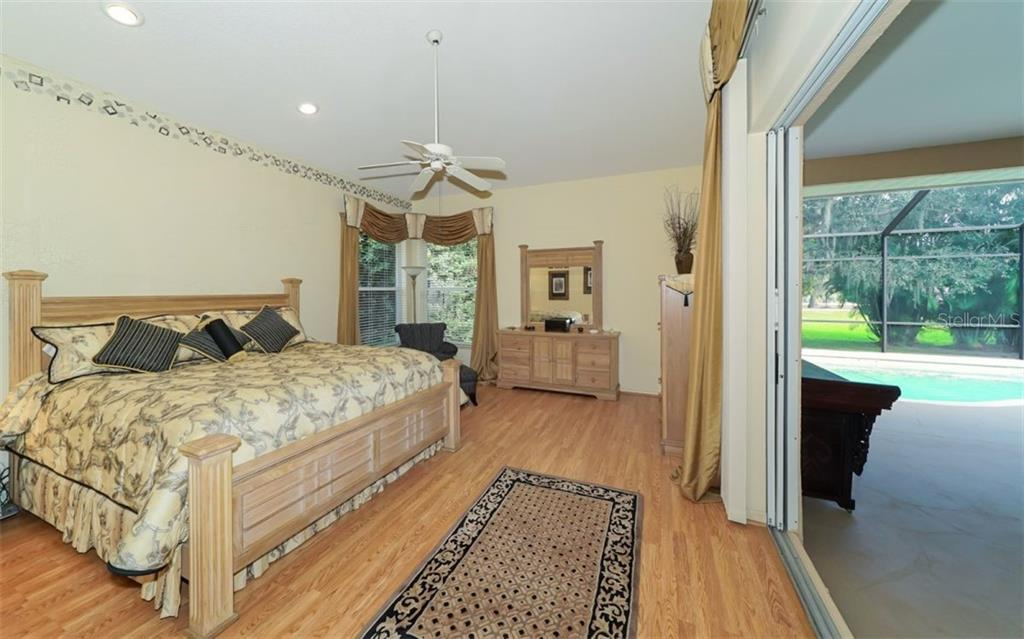 Master Suite with hardwood floors & large pocket sliding doors with direct access to pool & lanai. - Single Family Home for sale at 6125 Varedo Ct, Sarasota, FL 34243 - MLS Number is A4420656