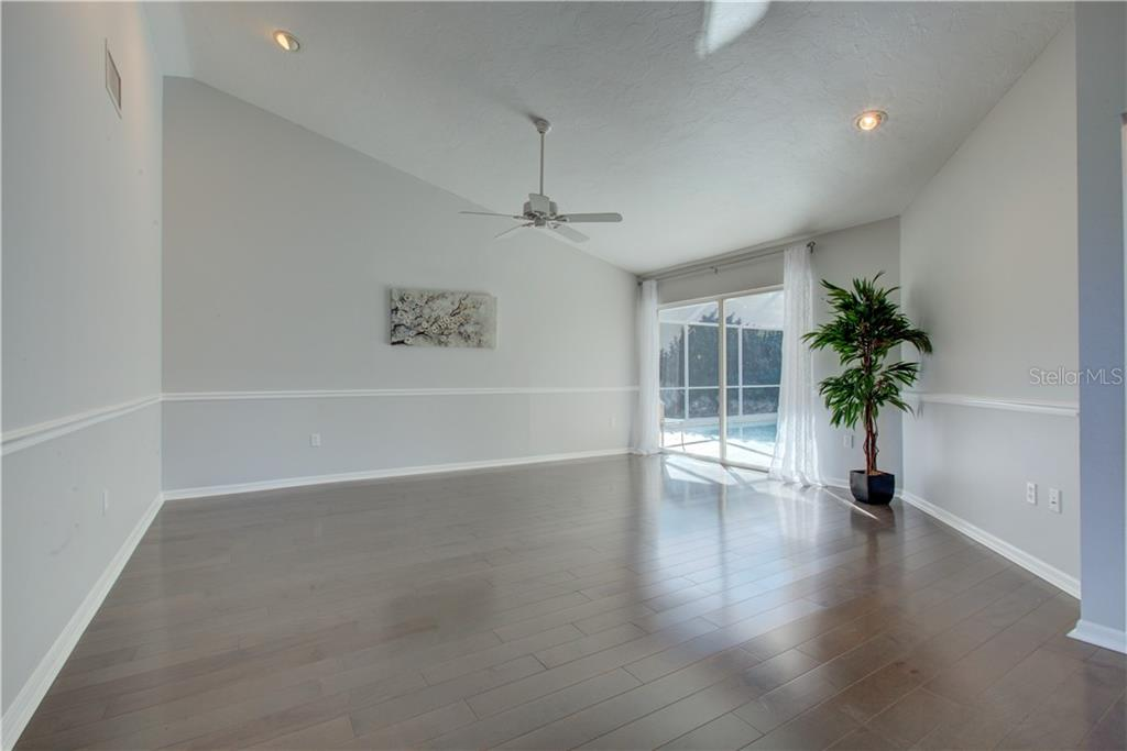 Spacious light and airy Living Room with sliding doors to the pool area - Single Family Home for sale at 5167 Kestral Park Ln, Sarasota, FL 34231 - MLS Number is A4421162