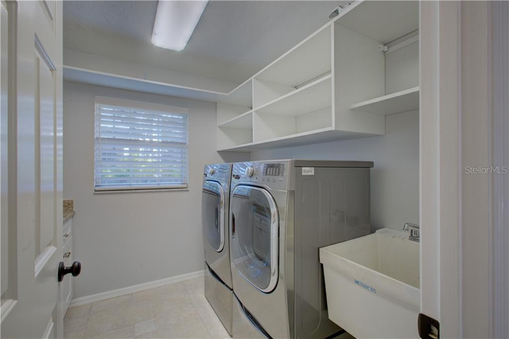 Laundry room with new washer and dryer, separate sink and plenty of shelving space - Single Family Home for sale at 5167 Kestral Park Ln, Sarasota, FL 34231 - MLS Number is A4421162