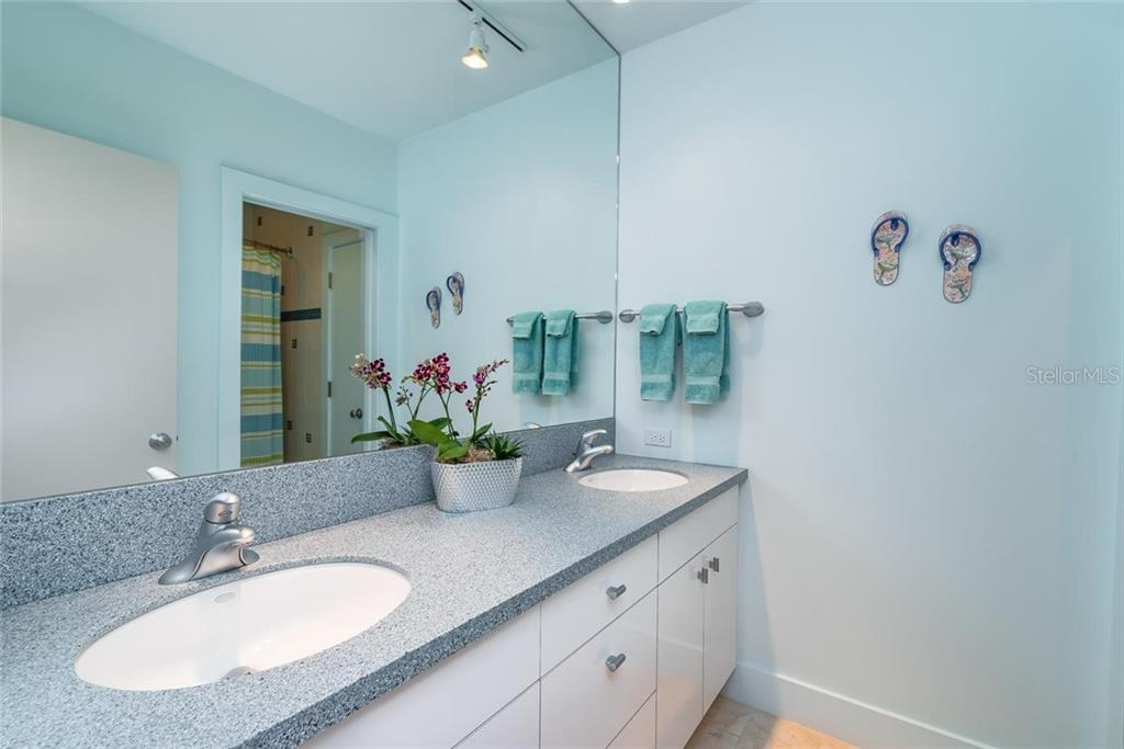 Guest bathroom with dual sinks and private w/c and shower. - Single Family Home for sale at 509 Venice Ln, Sarasota, FL 34242 - MLS Number is A4425092