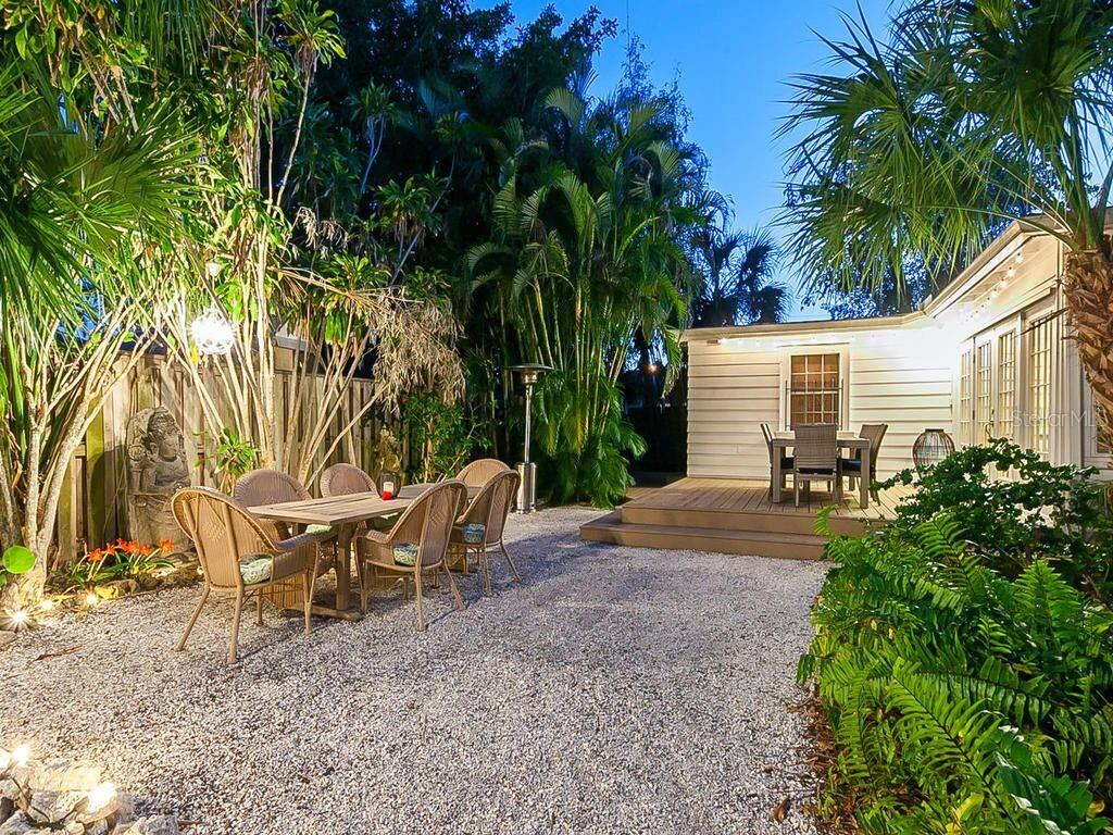 Deck with dining space and tropical backyard at dusk - Single Family Home for sale at 422 Garfield Dr, Sarasota, FL 34236 - MLS Number is A4425287