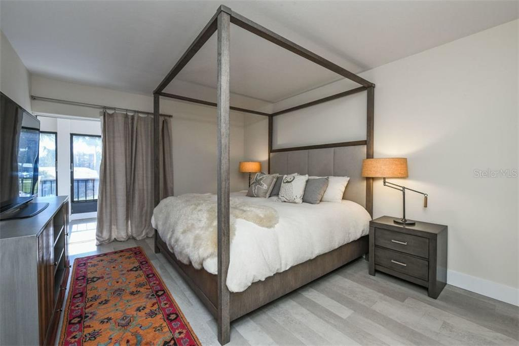 Handsome master bedroom includes drapes and rod, including blackout curtains.  Walk-in closet. - Condo for sale at 225 Hourglass Way #208, Sarasota, FL 34242 - MLS Number is A4425323