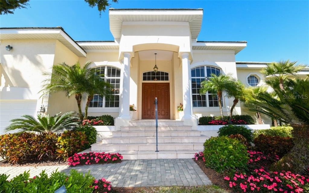 Beautiful Elevation with Travertine steps and Porch.  Notice the beautiful 8ft Mahogany Front Doors - Single Family Home for sale at 561 Ketch Ln, Longboat Key, FL 34228 - MLS Number is A4426280