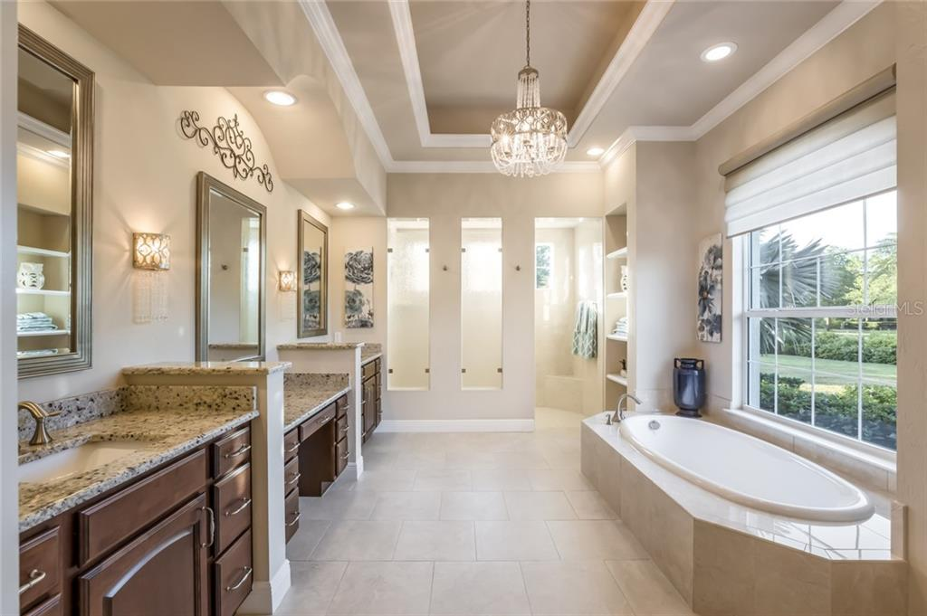 With separate granite dual vanities, large soaking tub, porcelain tile flooring and a walk-in roman shower with custom tile this bathroom has it all. - Single Family Home for sale at 19432 Newlane Pl, Bradenton, FL 34202 - MLS Number is A4432094