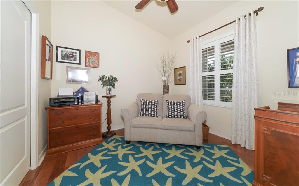 Den with wood floors, plantation shutters and pocket door leading to guest bath. - Condo for sale at 200 San Lino Cir #233, Venice, FL 34292 - MLS Number is A4440138