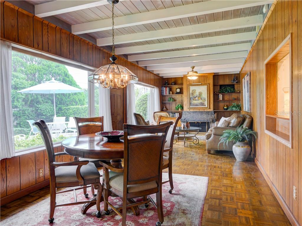 Florida room with plank and beam ceiling, with full array of windows overlooking Mirror Lake - Single Family Home for sale at 6605 Bluewater Ave, Sarasota, FL 34231 - MLS Number is A4440551