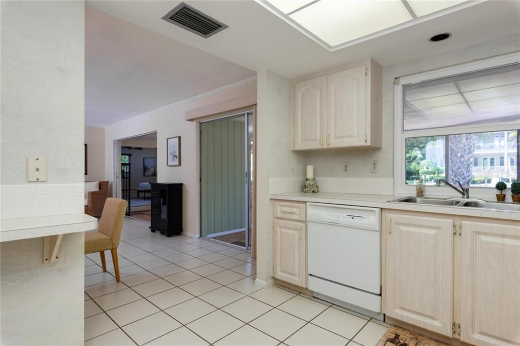 The dining area has a built in china cabinet and is open to the kitchen - Single Family Home for sale at 701 Norton St, Longboat Key, FL 34228 - MLS Number is A4440596