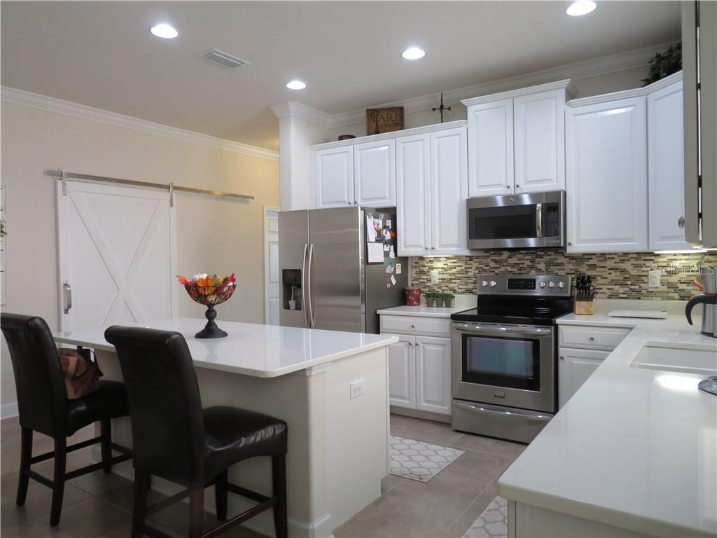 have guests sit at the breakfast bar while you prepare a meal. - Single Family Home for sale at 5727 Arbor Wood Ct, Bradenton, FL 34203 - MLS Number is A4448047