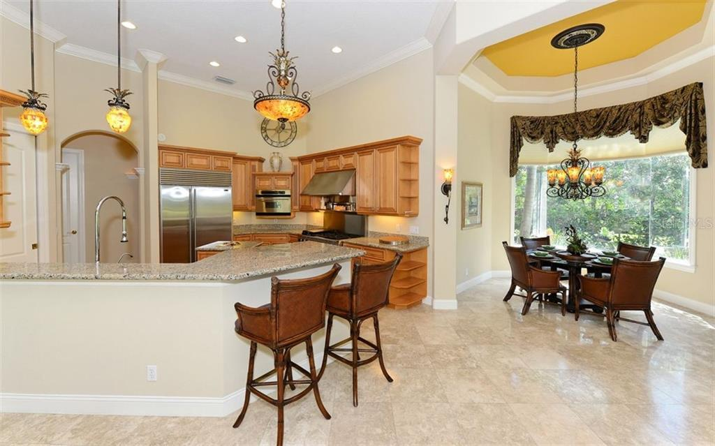 Kitchen offers a breakfast bar and nearby dinette for quick and casual meals. - Single Family Home for sale at 586 N Macewen Dr, Osprey, FL 34229 - MLS Number is A4451482