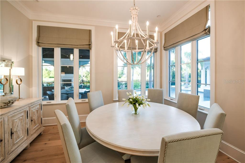 Gorgeous dining space with elegant chandelier, dining buffet with surrounding Jalousie windows. - Single Family Home for sale at 16119 Baycross Dr, Lakewood Ranch, FL 34202 - MLS Number is A4452632