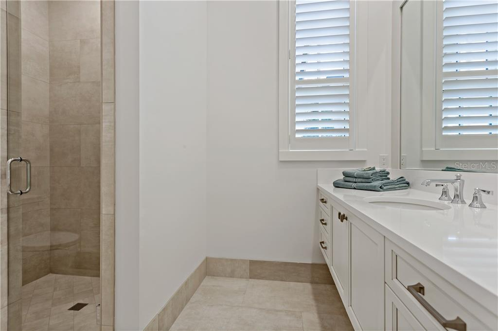 En-suite guest bath with rimless clear glass or and plantation shutters for light control. - Single Family Home for sale at 552 Eagle Watch Ln, Osprey, FL 34229 - MLS Number is A4454431