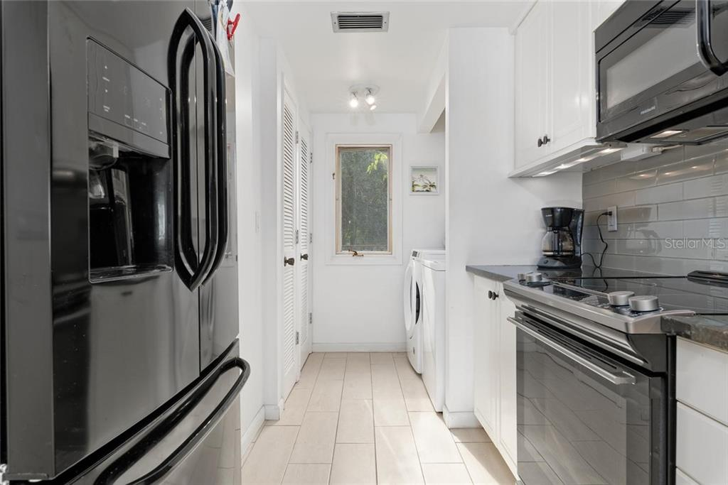 The well equipped kitchen continues to a nice laundry area with full size washer and dryer - Condo for sale at 490 N Shore Rd #7, Longboat Key, FL 34228 - MLS Number is A4461297