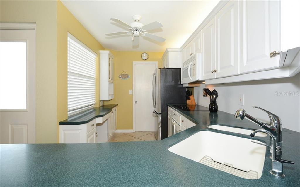 Kitchen with corian countertops & built-in desk. - Condo for sale at 1770 Benjamin Franklin Dr #706, Sarasota, FL 34236 - MLS Number is A4469463