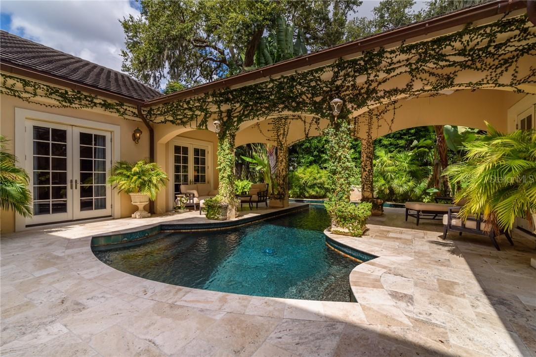 Enjoy a starlit evening lounging next to the fireplace, or swim in the welcoming 45 foot lap pool with custom glass tiles and fountain. - Single Family Home for sale at 1807 Oleander St, Sarasota, FL 34239 - MLS Number is A4475067