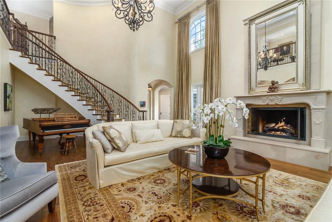 Two story living room with walnut plank flooring with spectacularly elegant fireplace with winding wrought iron staircase leading to 2nd floor bedroom suites and library! - Single Family Home for sale at 1807 Oleander St, Sarasota, FL 34239 - MLS Number is A4475067