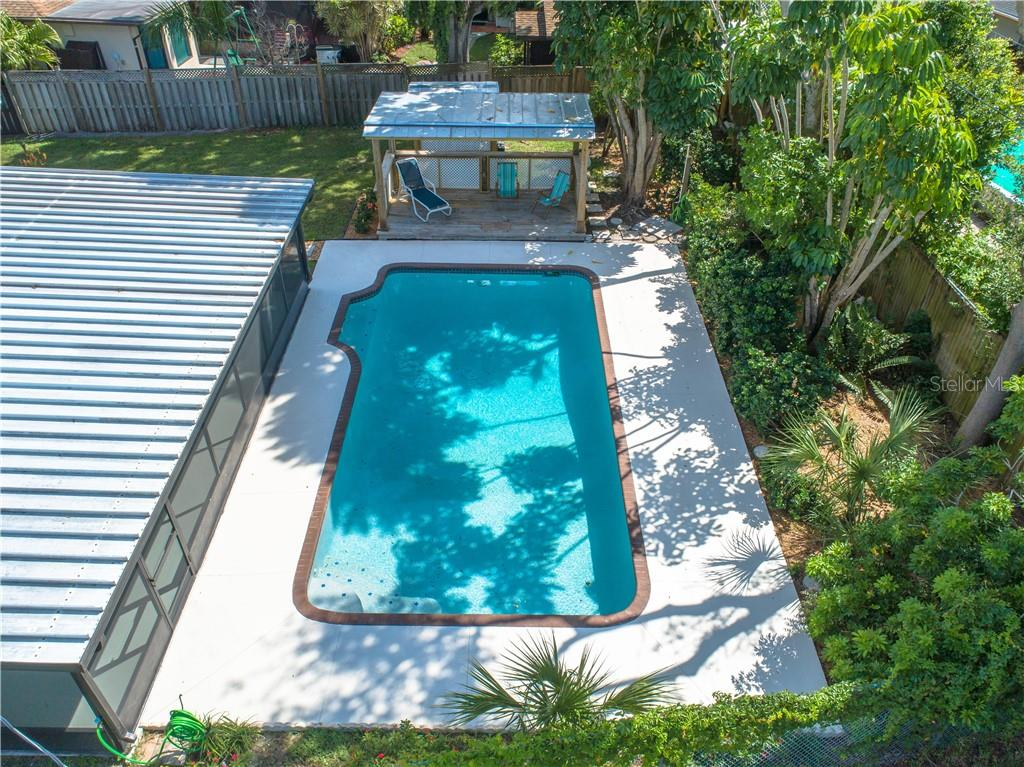 Aerial view of 15x30 pool with built in seating area, cabana, back porch, landscaping, and side yard. - Single Family Home for sale at 2408 Riverside Dr E, Bradenton, FL 34208 - MLS Number is A4480609