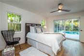 Master bedroom with sliders to lanai and swimming pool - Single Family Home for sale at 5115 Dewey Pl, Sarasota, FL 34242 - MLS Number is A4177178