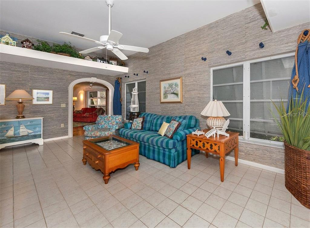 Family room features decorative shelving and arched doorway to formal living and foyer - Single Family Home for sale at 3509 Casey Key Rd, Nokomis, FL 34275 - MLS Number is N5915098