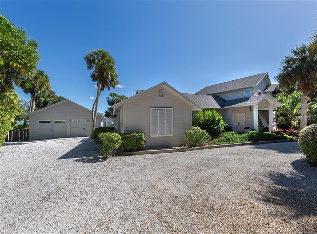 Side of home and garage with shell drive. - Single Family Home for sale at 3509 Casey Key Rd, Nokomis, FL 34275 - MLS Number is N5915098