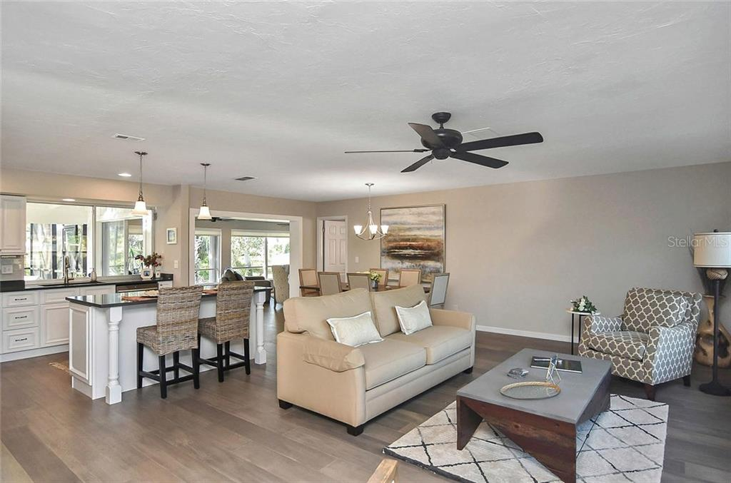 Kitchen, living room and dining room with new hardwood engineered flooring. - Single Family Home for sale at 405 Sunset Dr, Venice, FL 34285 - MLS Number is N5917234