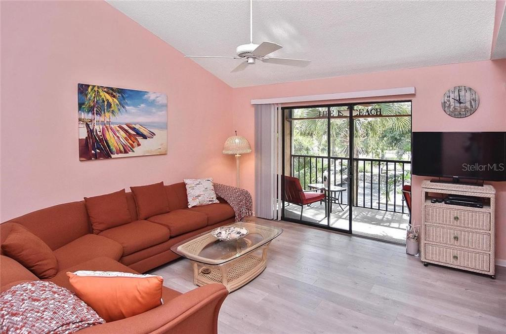 Living room with sliders to lanai - Condo for sale at 654 Bird Bay Dr E #201, Venice, FL 34285 - MLS Number is N6101101