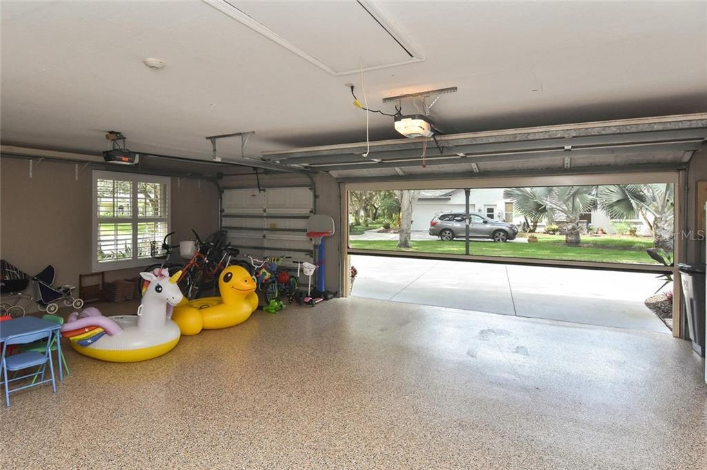 Garage has epoxy floor with an electric screen door - Single Family Home for sale at 7185 N Serenoa Dr, Sarasota, FL 34241 - MLS Number is N6109058