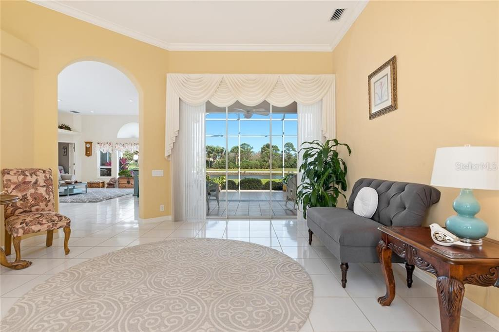 Living room with sliders to lanai - Single Family Home for sale at 886 Macaw Cir, Venice, FL 34285 - MLS Number is N6111692