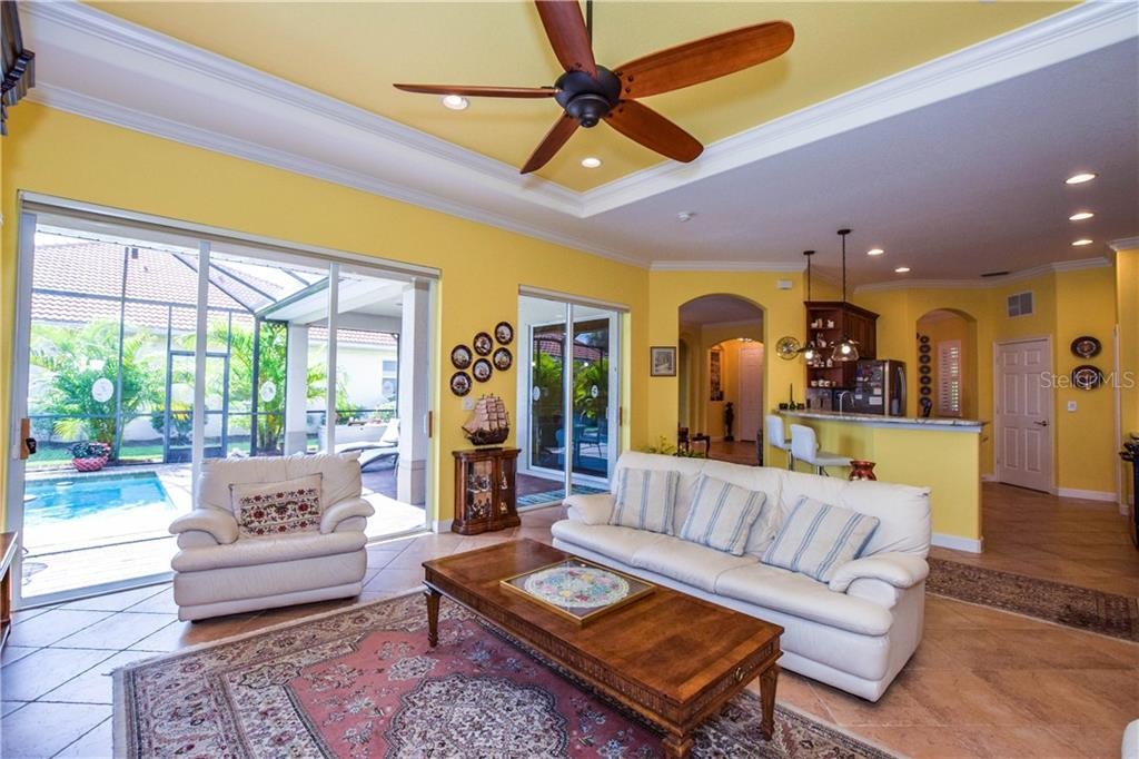 Family room with sliders to pool - Single Family Home for sale at 154 Rimini Way, North Venice, FL 34275 - MLS Number is N6112459