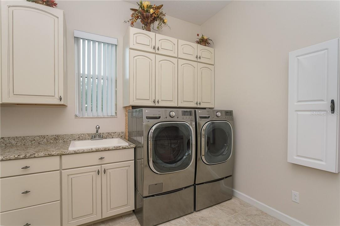 Spacious laundry room with storage galore, sink and built-in ironing board. - Single Family Home for sale at 1670 Maria St, Englewood, FL 34223 - MLS Number is N6113779