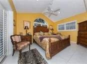 Beautiful bedroom with vaulted ceilings, plantation shutters, and French doors that open to the pool. - Single Family Home for sale at 620 Valencia Rd, Venice, FL 34285 - MLS Number is N6100912