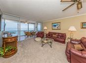 Living room with sliders to lanai - Condo for sale at 555 The Esplanade N #1004, Venice, FL 34285 - MLS Number is N6109326