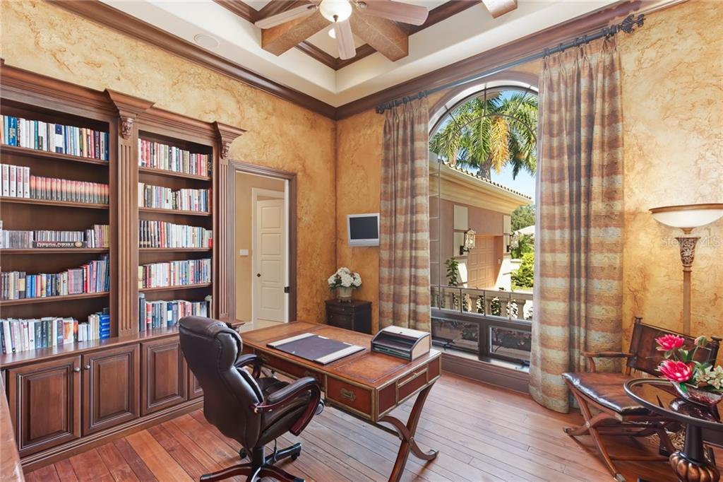 Office off the front foyer with built-in cabinets and shelves and walnut floors. - Single Family Home for sale at 7320 Barclay Ct, University Park, FL 34201 - MLS Number is A4200908