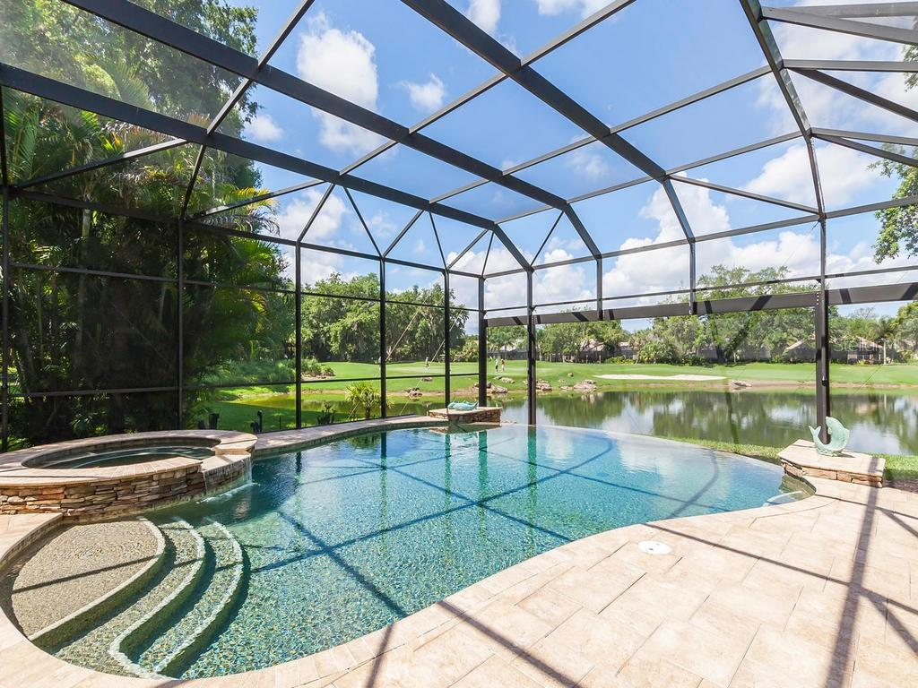 View from infinity edge pool over water to the green beyond.  A gorgeous wide expanse pool cage allows more view to the gorgeous scenery. - Single Family Home for sale at 12312 Newcastle Pl, Lakewood Ranch, FL 34202 - MLS Number is A4403090