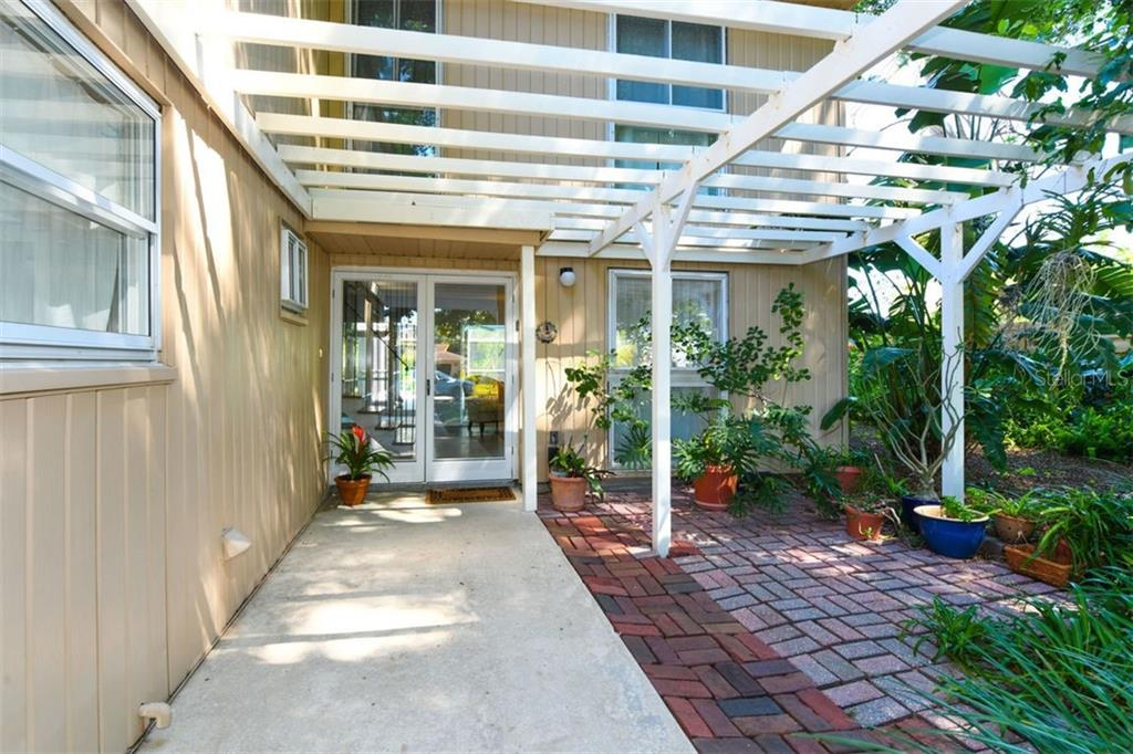 A charming pergola and double glass doors provide a warm welcome as you approach the home, - Single Family Home for sale at 7727 Westmoreland Dr, Sarasota, FL 34243 - MLS Number is A4430900