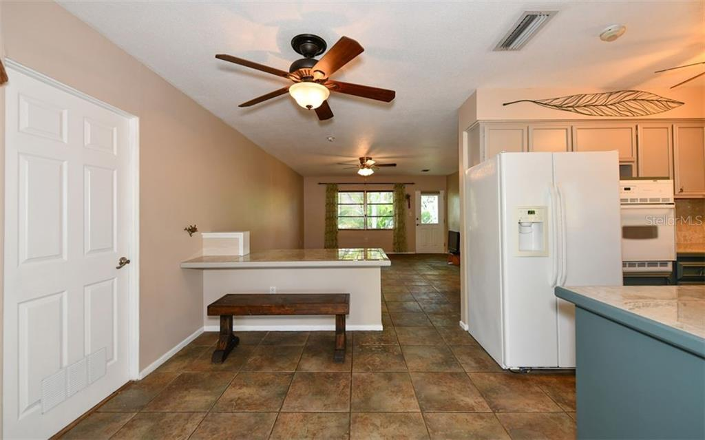 Looking from the back door into the dining area & living room. - Single Family Home for sale at 120 23rd Street Ct Ne, Bradenton, FL 34208 - MLS Number is A4438232