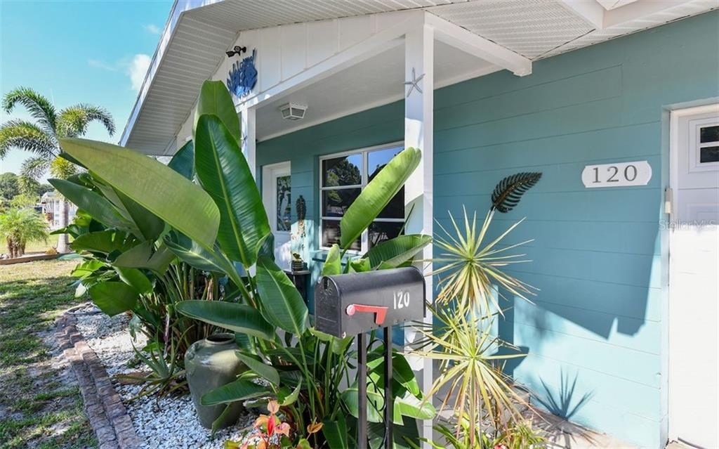 Tropical palms line the walkway to the front door. - Single Family Home for sale at 120 23rd Street Ct Ne, Bradenton, FL 34208 - MLS Number is A4438232