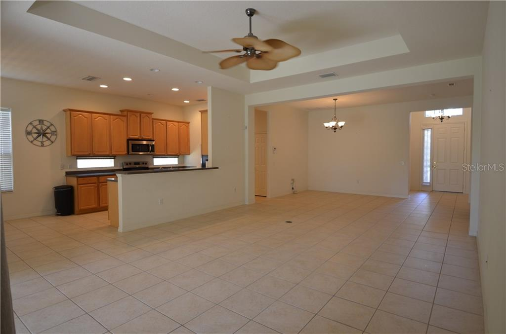 Huge living room with tile, electrical outlets in the floor. Dining room living room combo. View looking from sliding glass door to front door. - Single Family Home for sale at 3632 Summerwind Cir, Bradenton, FL 34209 - MLS Number is A4438762