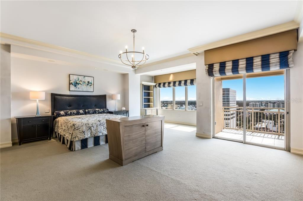 The master bedroom is incredibly spacious and has a pretty view of the city.  The piece of furniture in the center of the room has a TV that pops up. - Condo for sale at 1111 Ritz Carlton Dr #1704, Sarasota, FL 34236 - MLS Number is A4442192