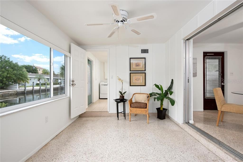 From the kitchen, across the dining area and into the bright Florida room that overlooks the canal. - Single Family Home for sale at 691 Tarawitt Dr, Longboat Key, FL 34228 - MLS Number is A4451584