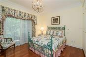 Guest House bedroom with closet and entertainment built-ins, and sliding glass doors to open lanai overlooking the lake and lush Floridian backdrop! - Single Family Home for sale at 3702 Beneva Oaks Blvd, Sarasota, FL 34238 - MLS Number is A4438878